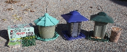 A suet feeder, individual cake and a box of cakes. To the right are three gravity feeders with black oil sunflower seeds as well as other seeds. Courtesy Ron Hellstern, photographer