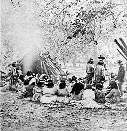 A Morning Council on the Merced Group of about twenty-six Native Americans seated and standing beside a cedar bark structure, near the Merced River, Yosemite Valley, 1872. (Title as printed on stereograph A Morning Concert on the Merced is in error.) [RL014217] Photo Courtesy US National Park Service